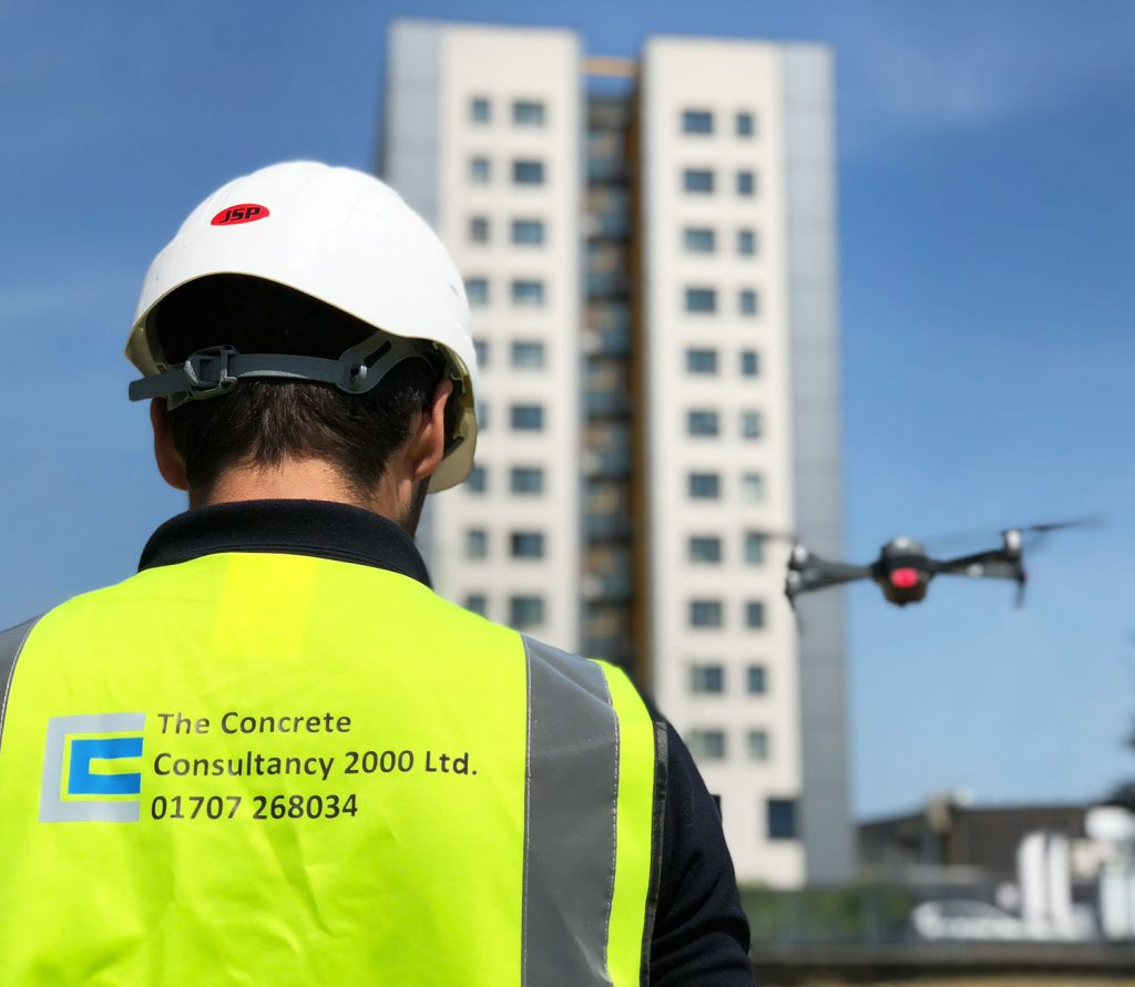 Concrete surveyor inspecting high rise building with drone